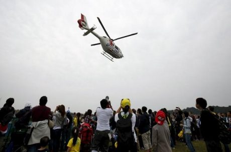 A medical helicopter carrying ART E-Motion Iodaracing Team MotoGP rioder Alex De Angelis of San Marino flies over spectators after Angelis crashed during fourth free practice session for Sunday's Japanese Grand Prix at the Twin Ring Motegi circuit in Motegi, north of Tokyo, Japan, October 10, 2015. REUTERS/Issei Kato
